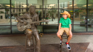 Young boy sitting next to a statue of Chet Atkins in Nashville, TN