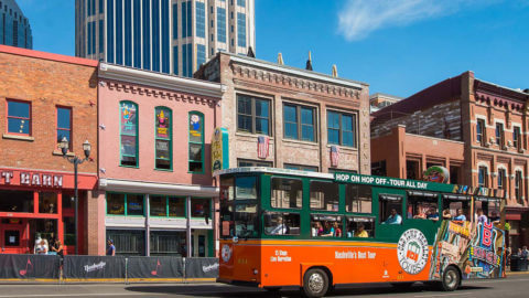 Old Town Trolley driving past storefronts on Lower Broadway in Nashville, TN