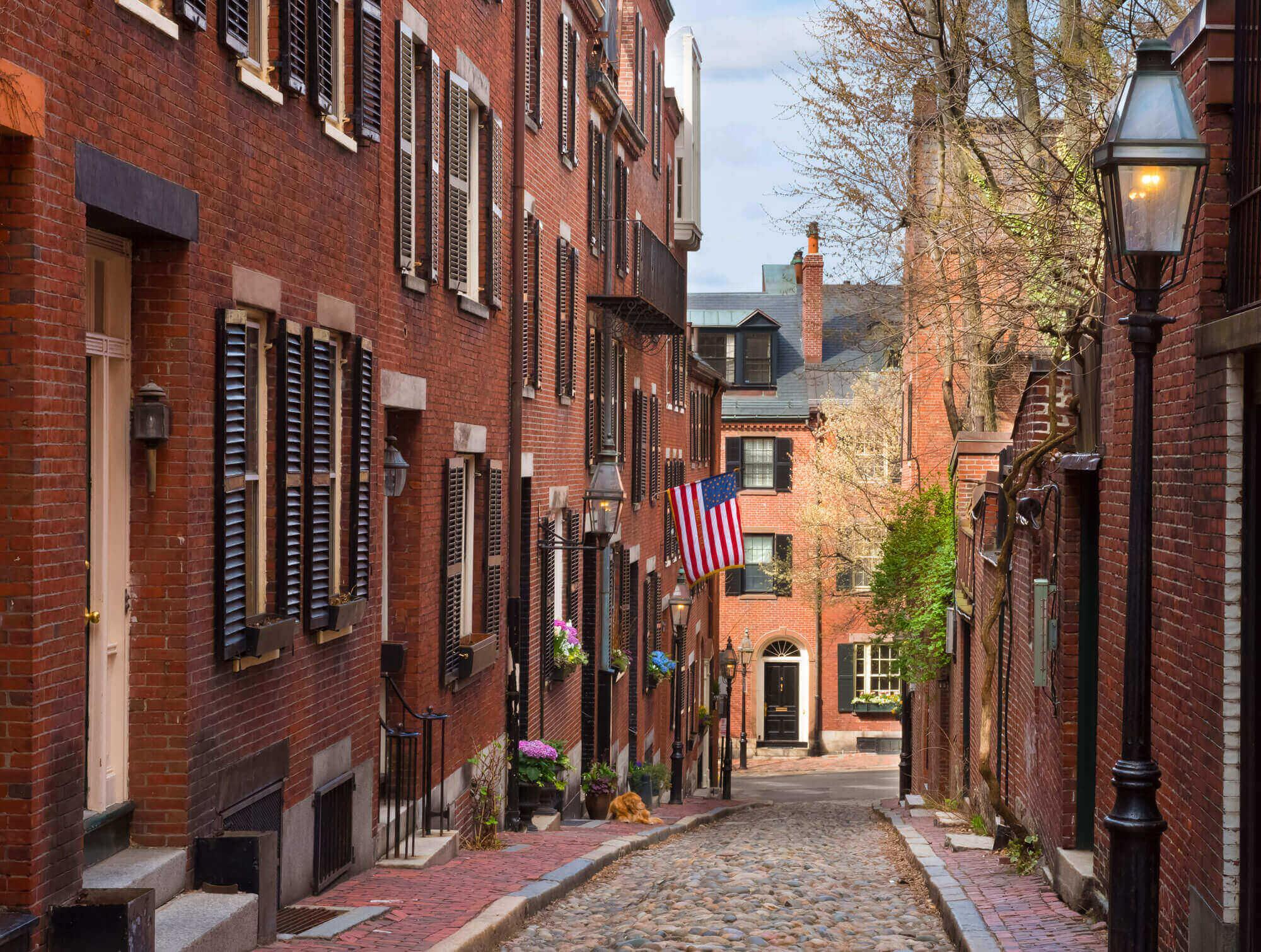 Looking downhill down narrow cobblestone acornt street in a residential neighborhood in Beacon Hill, Boston