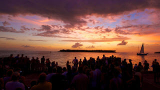 Large gathering of people on the pier in Mallory Square watching the sun set in Key West, FL