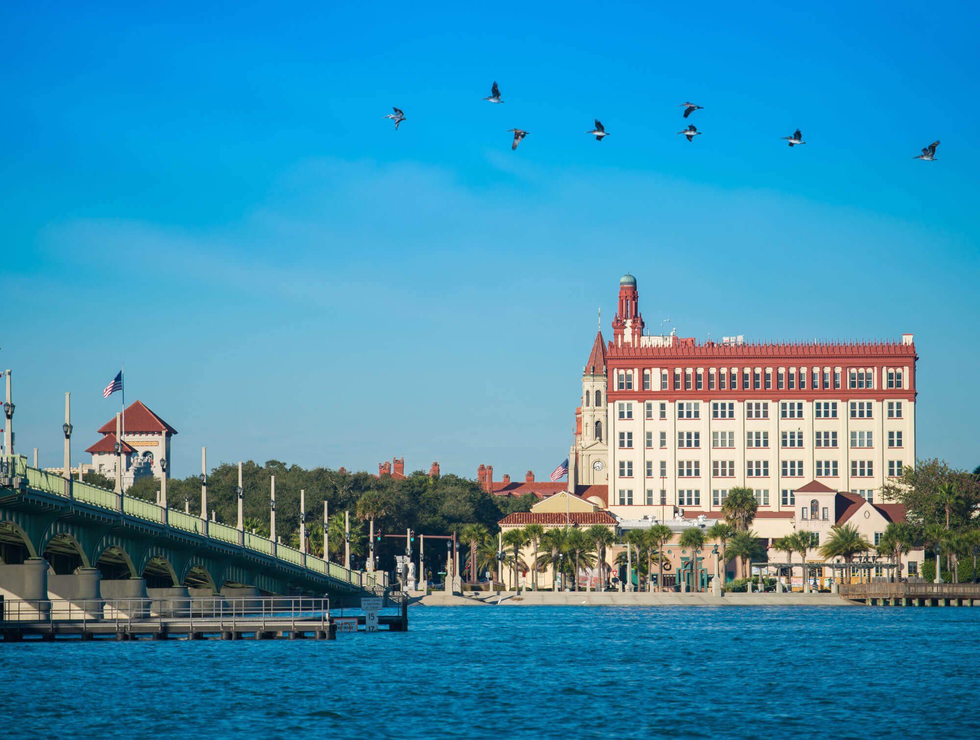 A view of St. Augustine from the Intercoastal Waterway of a large, old hotel in the center, the Bridge of the Lions off to the left and birds flying above