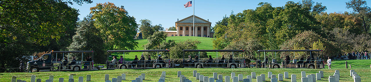 Arlington Tours vehicle driving past Arlington House in background and grave sites and trees in foreground
