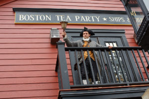 Boston actor dressed in colonial clothes and standing on a balcony ringing a bell; behind him is a sign that reads 'Boston Tea Party Ships & Museum'