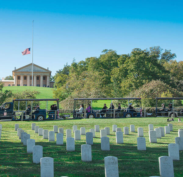 picture of arlington national cemetery vehicle driving past arlington house and tombstones in foreground