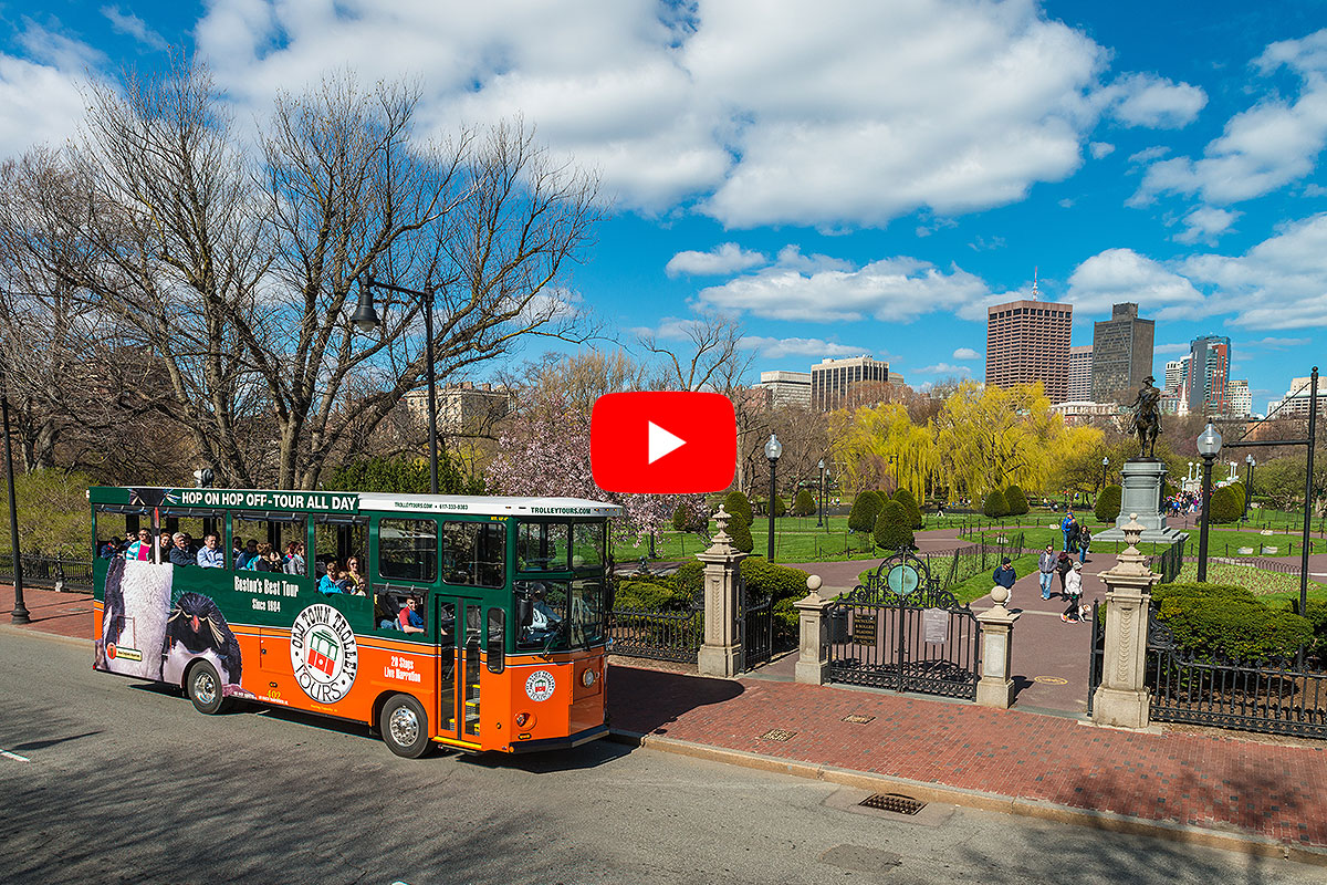 boston old town trolley driving past public garden and city skyline in background