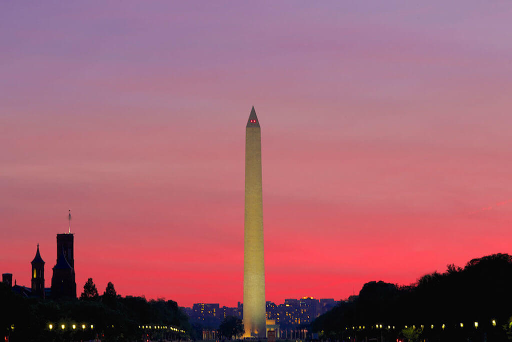 The Washington Monument set against a pink sky as night falls in Washington DC