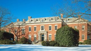 view of of front of large historic home made of brick with trees and snow in foreground