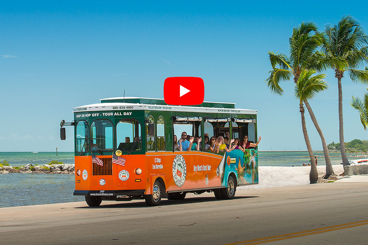 picture of old town trolley in key west driving past ocean and palm trees with a video play button symbol over image