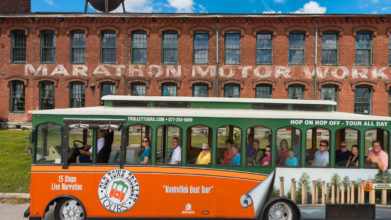 Old Town Trolley Tour passing in front of the old brick Marathon Automobile Company building