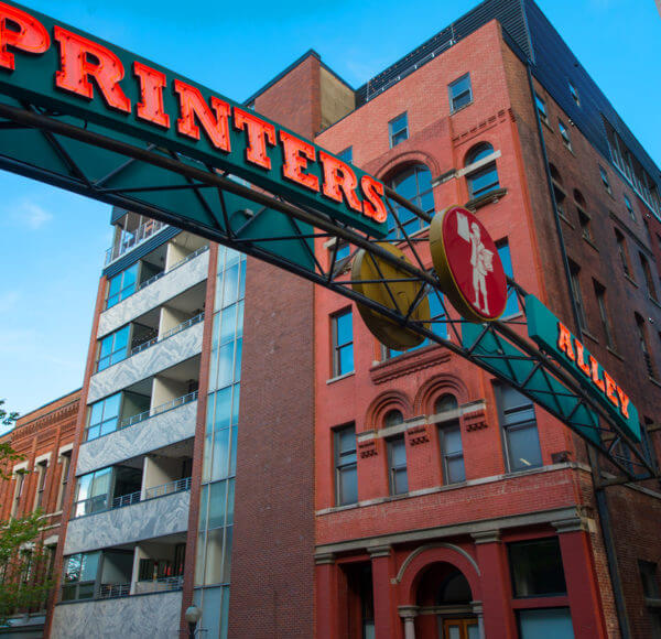 The entrance to Printers Alley in downtown Nashville, TN showing generic building in the background and an arch that reads 'printers ally' with a circle in the center showing a figure of a man holding paper