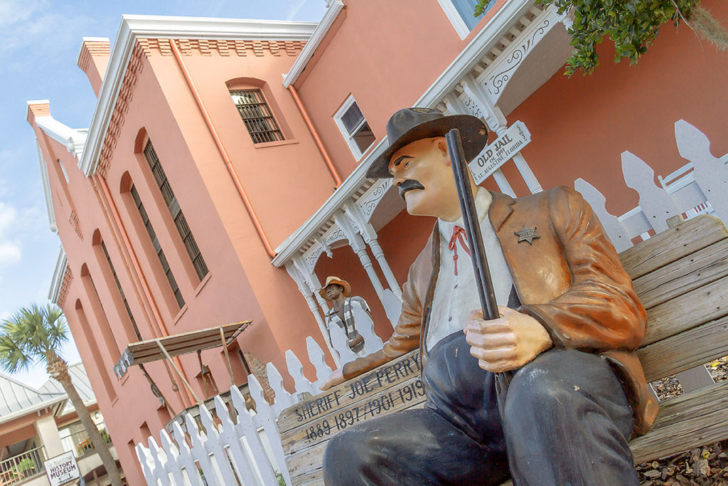 exterior shot of St. Augustine Old Jail and in the foreground is a statue of Sheriff Joe Perry sitting on a bench holding a shot gun with the words 'Sheriff Joe Perry, 1889 1897 / 1901 1919' painted on the bench