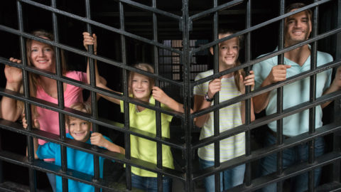 picture showing family of five smiling and standing behind bars inside a cell at the Old Jail Museum