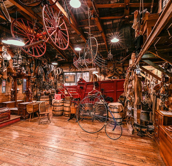 interior of oldest store museum featuring old bikes, barrels, portraits, trunks and may more items