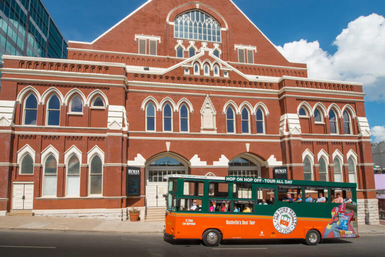 An Old Town Trolley Tour riding past the Ryman Auditorium in Nashville, TN