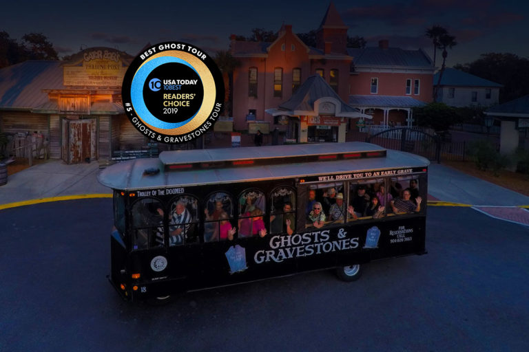 Night time picture of St. Augustine ghost trolley in front of the Old Jail and a Round logo that reads USA Today 10 BEST READERS' CHOICE 2019' and around logo, the words 'BEST GHOST TOUR, #5 - GHOSTS & GRAVESTONES TOUR'