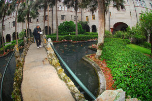 courtyard at Lightner Museum featuring a lady on a footbridge feeding koi fish swimming in pond and surrounded by foliage