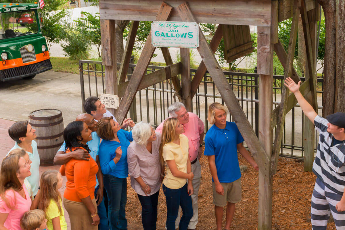 group of guests standing outside of Old Jail Museum in St. Augustine, FL while a tour guide points to the gallows