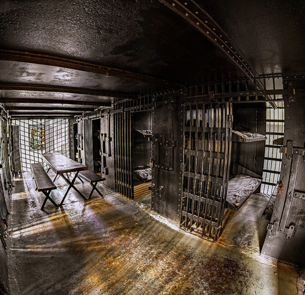 interior shot of the Old Jail featuring open cells with beds and a picnic table