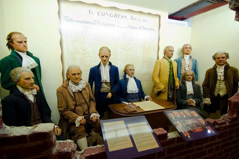 Wax likenesses of the signers of the Declaration of Independence in front of a large reproduction of the declaration itself inside Potter's Wax Museum in St. Augustine