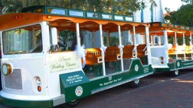 A modified wedding Old Town Trolley painted in white and green parked outside a church in St. Augustine, FL