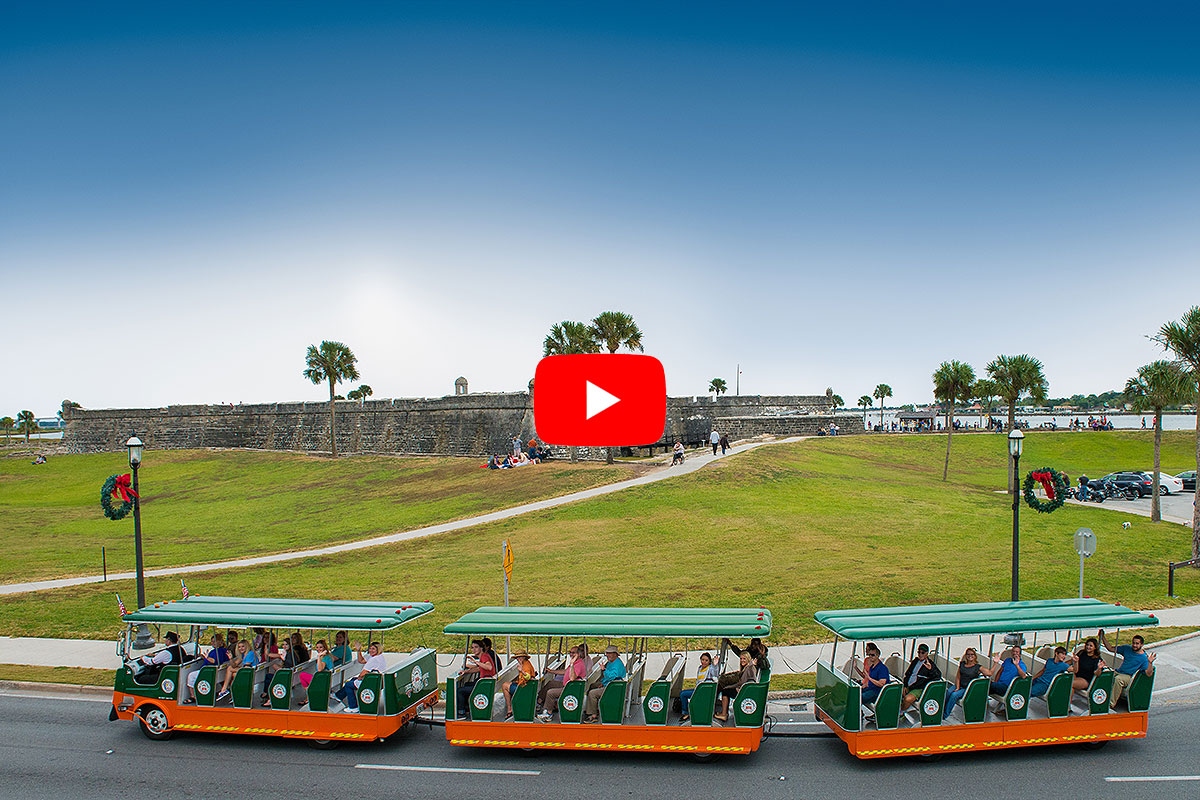 picture of a St Augustine old town trolley driving past Castillo de San Marcos fort in the background and a play video button in the foreground