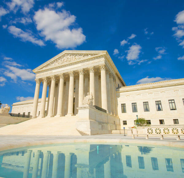 Front view of the U.S. Supreme Court building in Washington DC with pool in the foreground showing reflection of supreme court