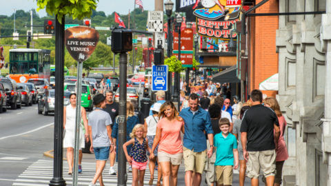 A street view of Nashville's Lower Broadway district teeming with people walking and cars