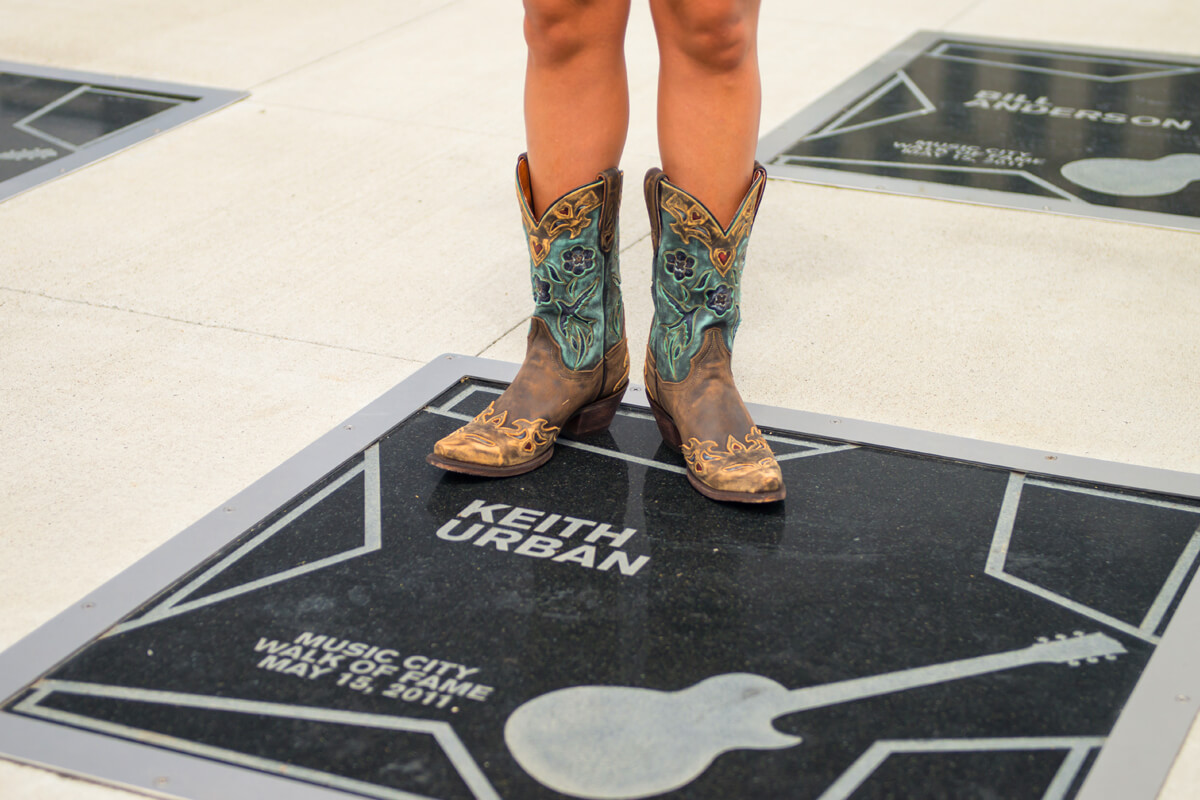 The legs of a girl in modern fashionable cowboy boots standing next to Keith Urban's star on the Music City Walk of Fame in Nashville, TN