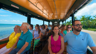 Smiling patrons in bright colored clothes riding next to the beach in Key West during an Old Town Trolley Tour