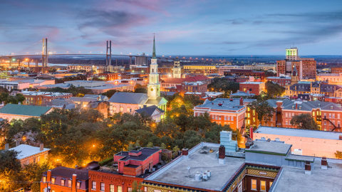 Savannah, Georgia skyline at dusk featuring rooftops in the foreground and Talmadge Bridge in the background