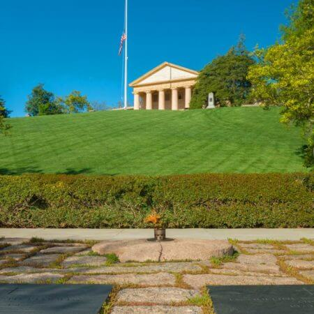 Image of the flat stones and memorial plaque dedicated to John F. Kennedy that surrounds the Eternal Flame in the Arlington National Cemetery