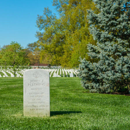 Close-up of the headstone General John J. Pershing overlooking rows of white headstones in Arlington National Cemetery