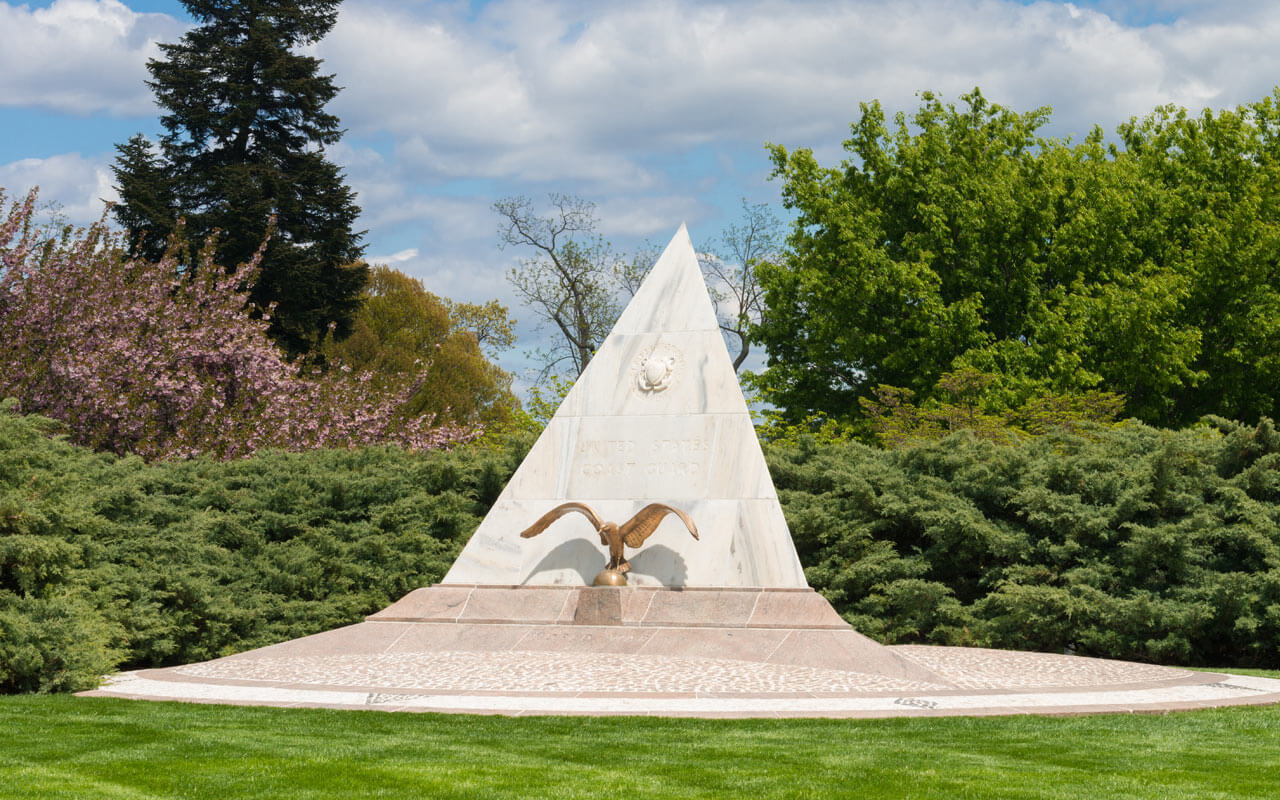 The U.S. Coast Guard Memorial which appears as a triangular slab of marble emblazoned with the Coast Guard Crest accompanied by a bronze eagle in Arlington National Cemetery