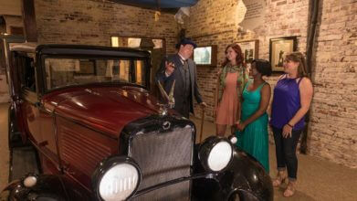 Image of a maroon colored vintage 1920s era automobile next to three guests and a man in a period accurate blue 3-piece suit laughing with a cigar in his hand in the American Prohibition Museum in Savannah,GA