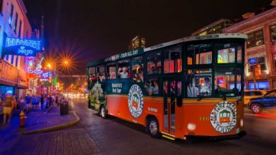 Night time picture of Old Town Trolley packed with people waving and smiling down Lower Broadway in Nashville, TN