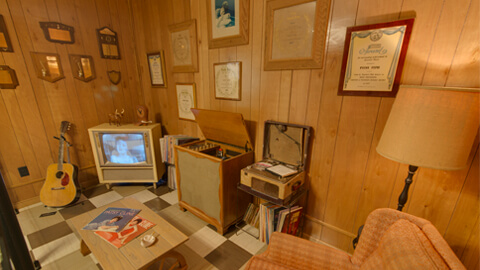 museum display at Patsy Cline Museum showing vintage living area with wood paneling, TV, guitar, lamp, and framed artwork on wall