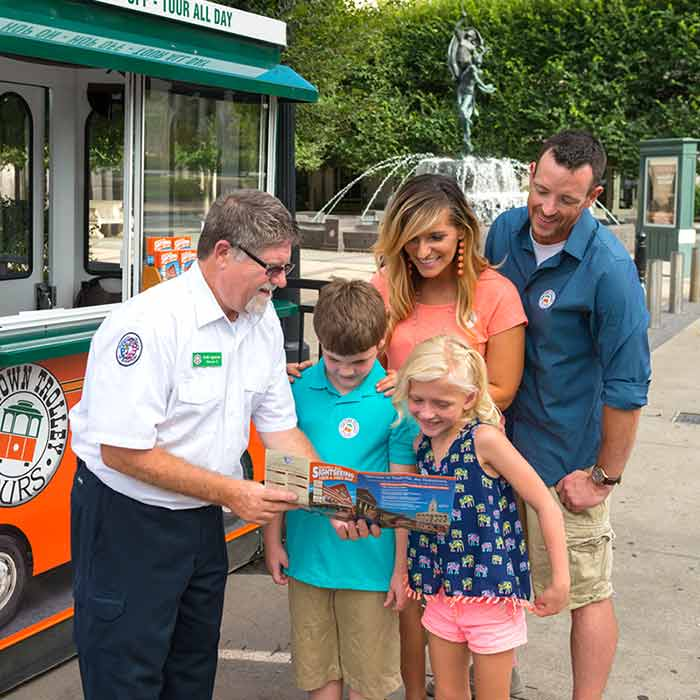 old town trolley tours sales representative showing a brochure to a family consisting of wife, husband, young son and young daughter with ticket booth and fountain in the background