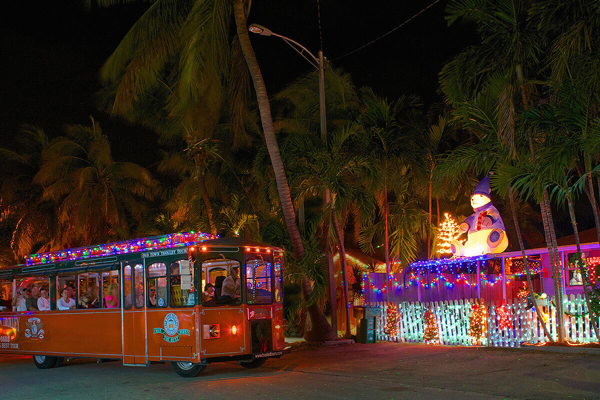 picture of key west old town trolley at night driving past a house decorated with holiday lights