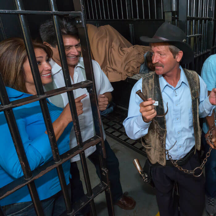 two guests standing behind bards inside cell at Old Jail Museum in St. Augustine, FL while listening to a tour guide dressed like a sheriff and holding handcuffs
