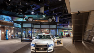 national law enforcement museum exhibit featuring a police car in the center with a door open and the words 'Indiana State Police' and in the background, glass case with a truck mounted on the top