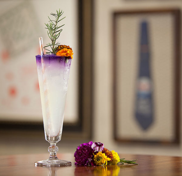 an alcoholic beverage and flowers on a table