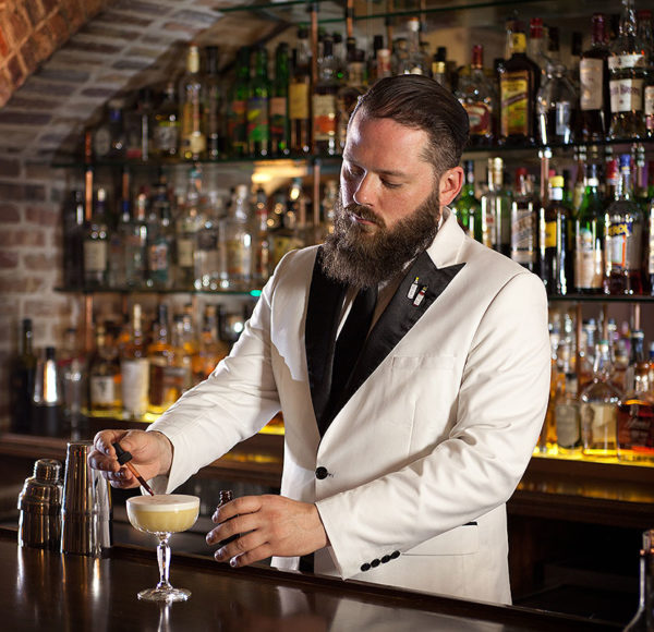 picture showing a bartender in suit and tie fixing an alcoholic beverage with rows on liquor bottles on glass shelves on display behind him