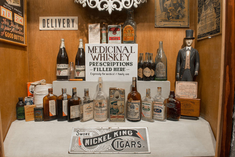 museum showing two rows of whiskey bottles, several art pieces on the wall, a sign that reads 'delivery', a sign that reads 'smoke nickel king cigars', and a sign that reads 'medicinal whiskey prescriptions filled here, expressly for medical & family use'