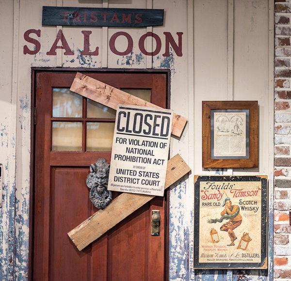 picture showing wood and brick wall, a door with the word 'saloon' above it, two boards blocking door and a sign that reads 'closed for violation of national prohibition act by order of United States District Court'