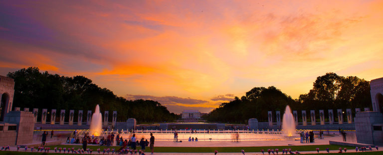 Sunset picture of WWII memorial in Washington DC made up of columns and fountains and the Lincoln Memorial far off in the background