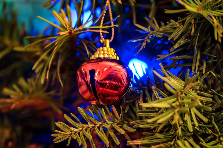 close up picture of a Christmas tree with holiday lights and a bell ornament