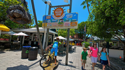 guests walking through Key West's Mallory Square made up of food booths and carts. In the background, there's a statue of a man riding on a bicycle, two barrels, a sign that says 'Mallory Square' and tables and chairs
