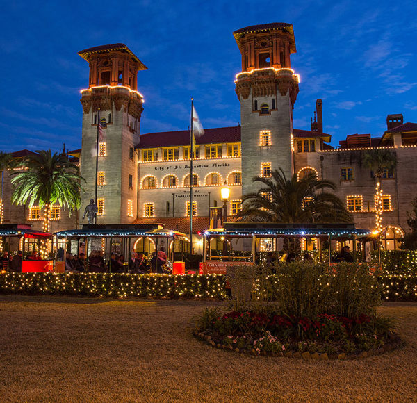 St. Augustine old town trolley driving past lightner museum at night decorated with holiday lights