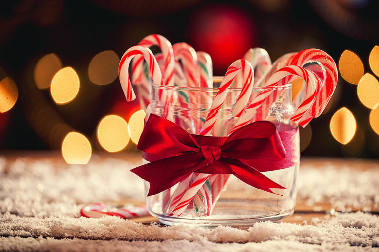 glass container wrapped in a ribbon and holding candy canes; in the background are holiday lights
