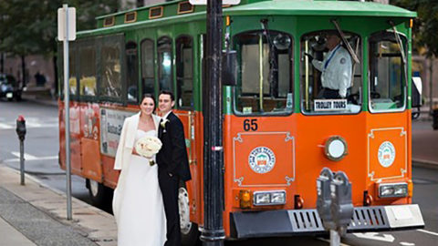 bride and groom standing in front of boston trolley